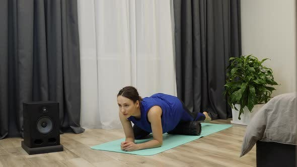Woman stretches thigh muscles using yoga roller.