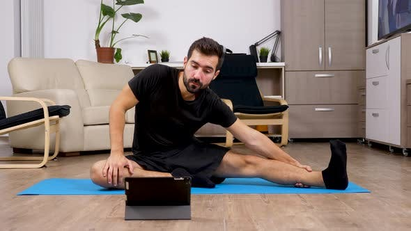 Man Repeating Exercises After What He Sees on a Digital Tablet PC