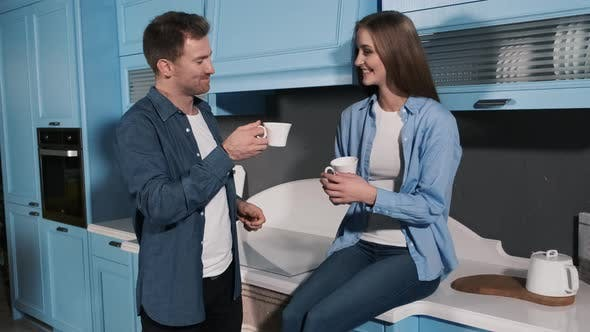 Thumbnail for Happy Couple Drink Morning Coffee in the Kitchen. Young Man and Woman Standing in Kitchen Talking