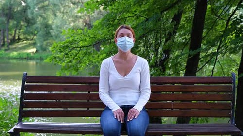 Pandemic, Coronavirus Quarantine. Young Woman Sits on a Park Bench Alone During an Epidemic