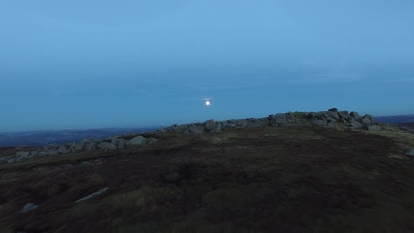 Thumbnail for Aerial shot of men climbing boulders while bouldering at night under a full moon.