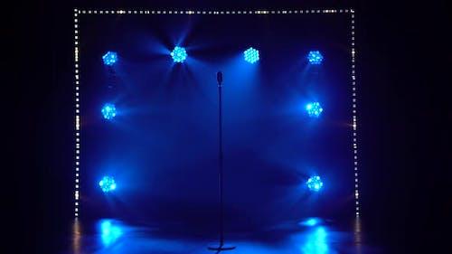 Das Studio verfügt über ein Mikrofon-Set im Retro-Stil gegen dynamische blaue Neonstrahler und Rauch. Jahrgang