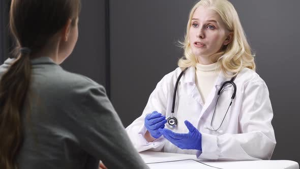 Serious Young Female Doctor Talking To a Female Patient