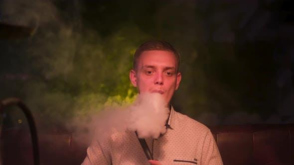 Man producing rings of smoke