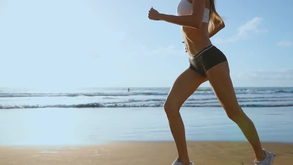Cover Image for Beautiful Sporty Women in White Sneakers Running Along a Beautiful Sandy Beach, Healthy Lifestyle