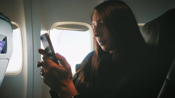 Woman Sitting Near Airplane Window and Using Mobile Phone During Flight.