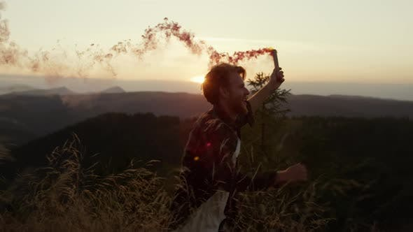 Male Hipster Running in Field with Smoke Bomb
