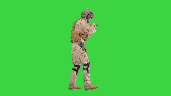 Armed Soldier in Camouflage Walking and Aiming with a Hand Gun on a Green Screen Chroma Key