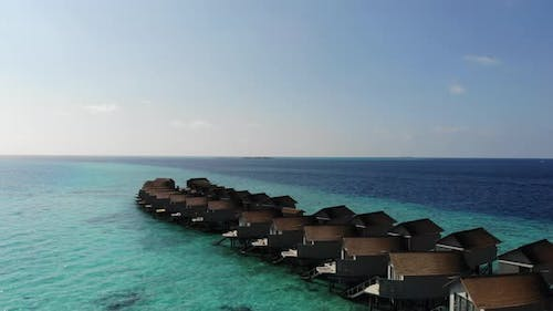 Aerial view villas over water on tropical island resort in Maldives with turquoise sea