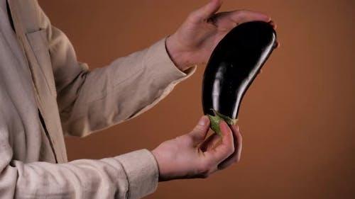 Man Holding an Eggplant Aubergine, Close-up