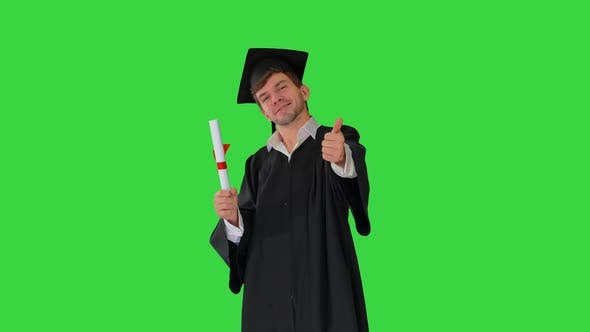 Thumbnail for Happy Male Student in Graduation Robe Posing with His Diploma and Showing Thumbs Up on a Green