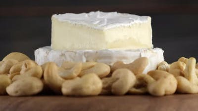 camembert or brie cheese with cashews close up, rotation. Soft, creamy cheese. 4K UHD video