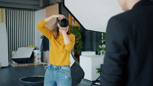 Professional Photographer Taking Pictures of Male Model Using Camera in Studio