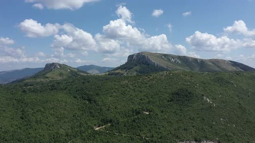 Ascending over the forest and hills under Carpathian Stol mountain 4K aerial video