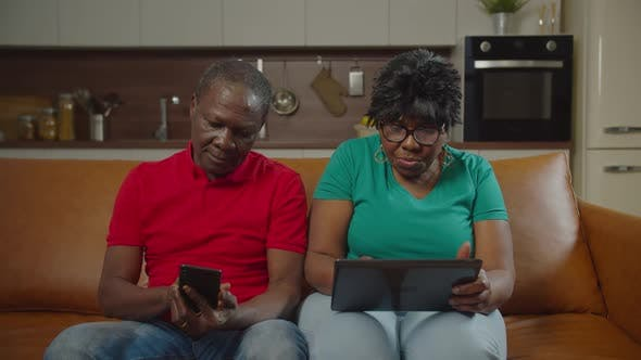 Senior African Couple Networking with Gadgets Indoor