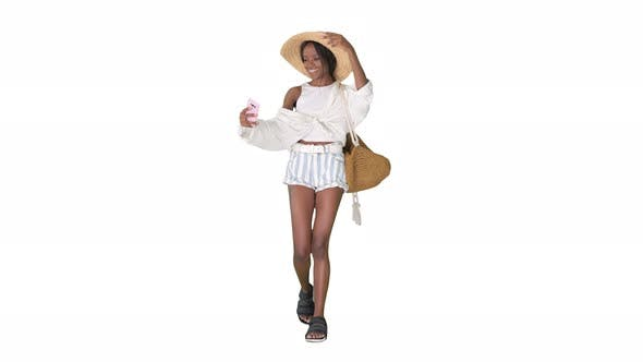 Smiling African American Woman in a Straw Hat Taking Selfie While Walking on White Background.
