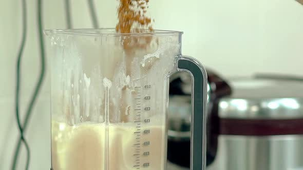 Cook Pours Cocoa Into the Mixer