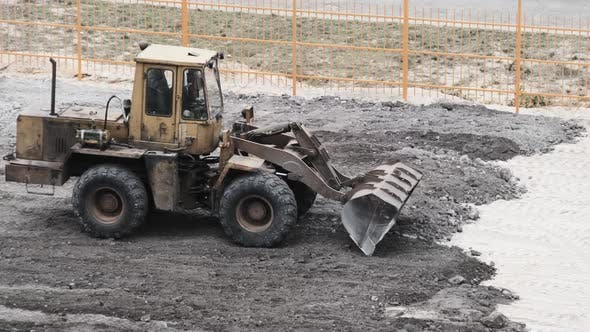 Thumbnail for An Old Bulldozer on Rubber Wheels Works on Construction Site