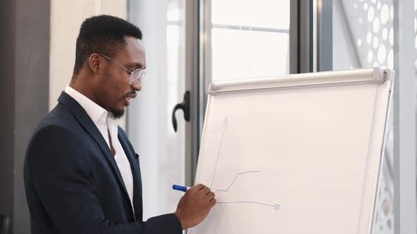 African American Architec Engineer Drawing Plan on Flip Chart at Office