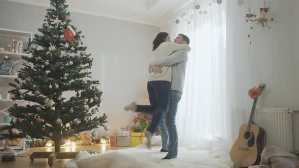 Thumbnail for Wide Shot Portrait of Happy Caucasian Man Hugging and Spinning Cheerful Woman on Christmas Eve at