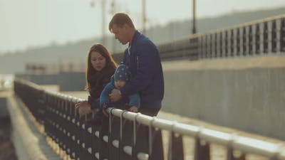 Parents Talk on the Pier at the Parapet the Baby is Sitting