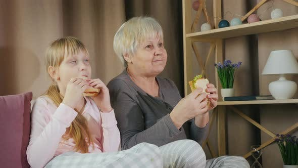 Thumbnail for Active Elderly Woman with Granddaughter Together Watching TV and Eating Sandwiches
