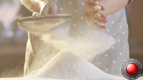 Woman Sifting Flour With A Sifter In The Kitchen With Sun Shining In Slow Motion Shot On Red Camera