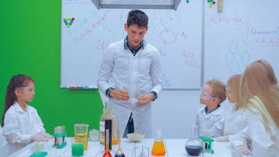 Pupils and Teacher Watching Experiment in Science Class