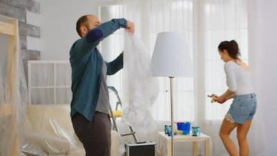 Man Wrapping Lamp with Plastic Poil