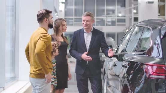 Cover Image for Confident Male Car Dealer Advertising New Car To the Caucasian Family in Automobile Showroom
