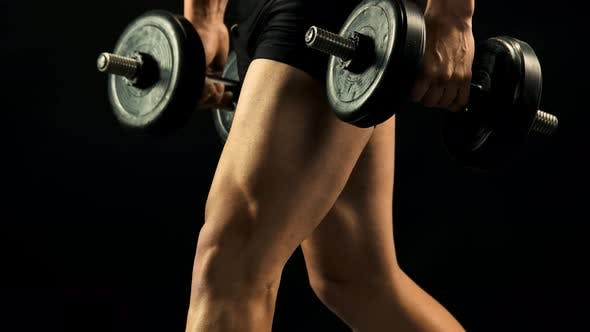 Junger Sportler macht Kniebeugen mit Hanteln