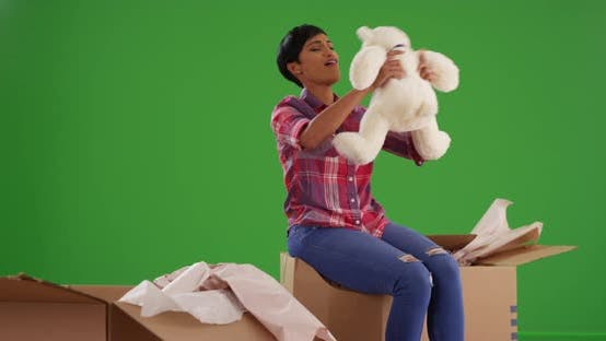 Black female unpacking box in new home, excited to find teddy bear on green screen