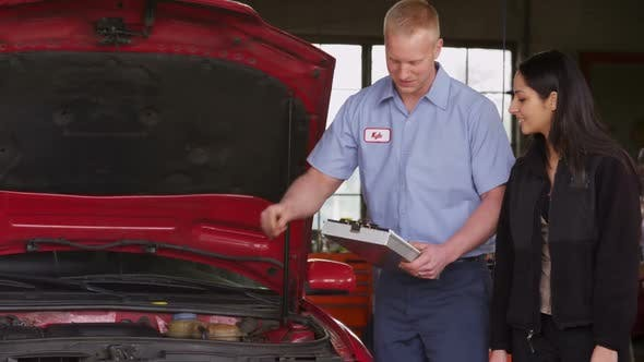 Thumbnail for Mechanic in auto repair shop works with customer