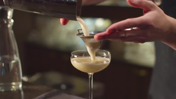 Thumbnail for Bartender Pours Alcohol in Glass Through a Sieve at the Bar