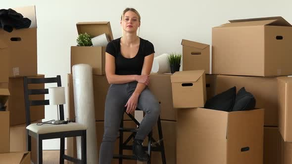 Thumbnail for A Moving Woman Sits on a Chair and Looks Seriously at the Camera in an Empty Apartment