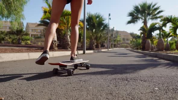 Cover Image for Beautiful Young Girl Rides on Road Near Beach and Palm Trees on Longboard in Slow Motion