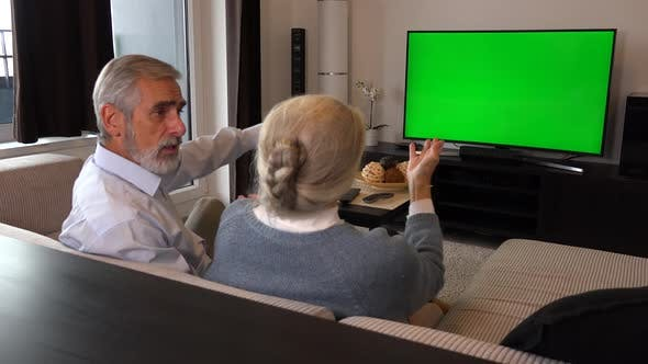 Thumbnail for An Elderly Couple Sits on A Couch in A Living Room, Watches Tv with A Green Screen and Argues