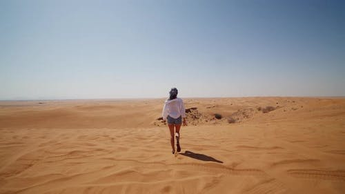 Young Woman in Jeans and White Shirt Walking Down Sand Dune in the Desert