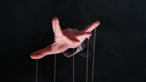 Hand of Dictator in a Business Suit with Strings on the Fingers To Control the Puppet