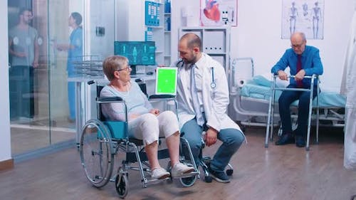 Doctor with Green Screen Tablet in Rehabilitation Center