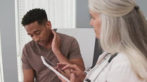 Attractive black male patient paying doctor visit with neck pain