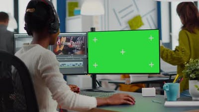 Black Videographer Using Computer with Chroma Key