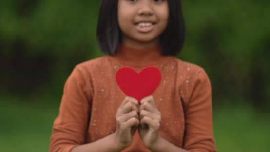 Girl holding red paper hearts