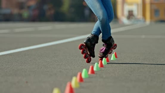 Legs of an Athlete in Roller Skates Go Around the Cones, Freestyle Butterfly. Professional Freestyle