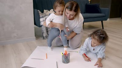 Mother and Daughters Drawing on Paper at Home