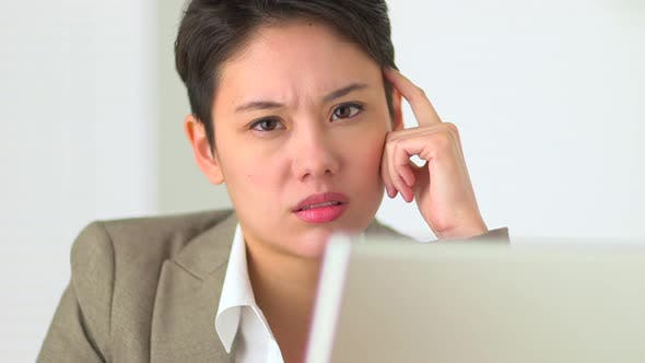 Thumbnail for Asian Business woman concentrating while working on laptop