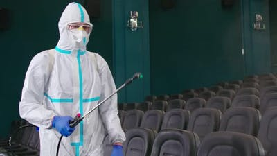 Worker in Antivirus Uniform Spraying Disinfectant at Cinema