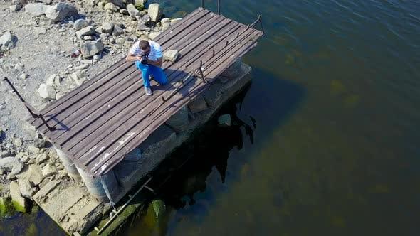 Thumbnail for Man Taking Photos Near Pond