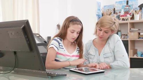 Teenager-Mädchen wischen den Bildschirm von einem Tablet während Ihre Mutter sieht auf die Bildschirm
