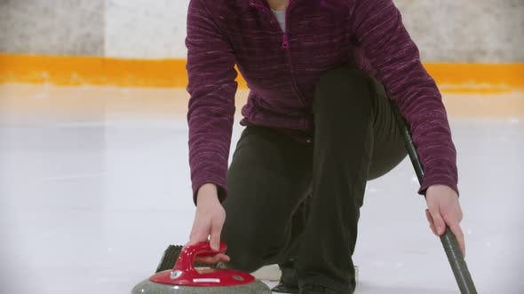 Thumbnail for Curling Training on Ice Rink - a Young Woman in Glasses Pushes Off From the Stand with a Stone